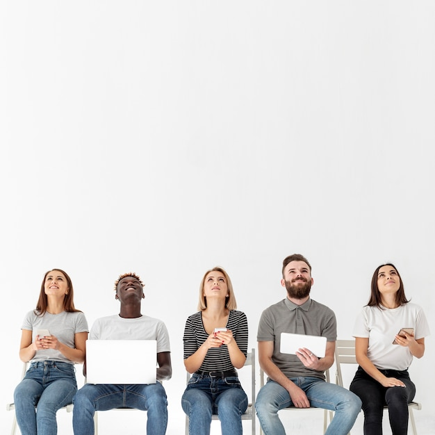 Młodzi Przyjaciele Na Krzesłach Za Pomocą Nowoczesnych Urządzeń Darmowe Zdjęcia