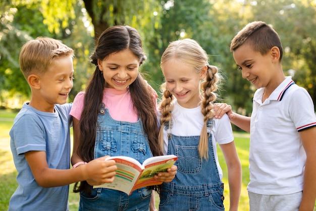 Młodzi przyjaciele razem czytając książkę Darmowe Zdjęcia