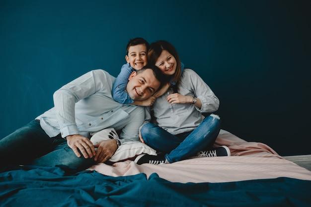 Młodzi rodzice leżą z synem na łóżku Darmowe Zdjęcia
