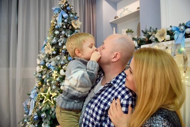 Młodzi Rodzice Z Synem Uśmiechając Się Do Kamery Podczas świętowania Bożego Narodzenia W Domu. Premium Zdjęcia
