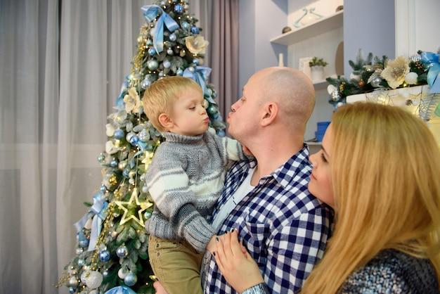 Młodzi Rodzice Z Synem Uśmiechając Się Do Kamery Podczas świętowania Bożego Narodzenia. Premium Zdjęcia
