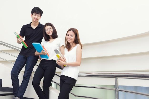 Młodzi Ucznie Stoi Z Mieniem Rezerwują W Bibliotece. Premium Zdjęcia