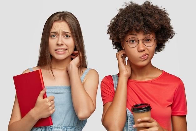 Młodzi Uczniowie Z Zawstydzonej Rasy Mieszanej Patrzą Ze Zdziwieniem Darmowe Zdjęcia