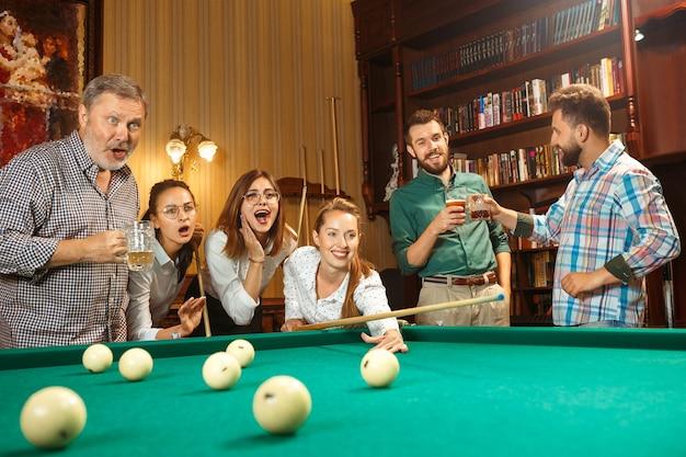 Młodzi Uśmiechnięci Mężczyźni I Kobiety Grają W Bilard W Biurze Lub W Domu Po Pracy. Współpracownicy Zajmujący Się Rekreacją. Przyjaźń, Rozrywka, Koncepcja Gry. Darmowe Zdjęcia