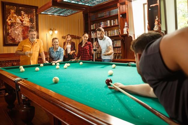 Młodzi Uśmiechnięci Mężczyźni I Kobiety Grają W Bilard W Biurze Lub W Domu Po Pracy. Współpracownicy Zajmujący Się Rekreacją Darmowe Zdjęcia