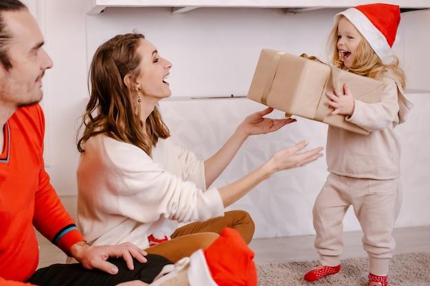 Młodzi Uśmiechnięci Rodzice Dając Trochę Zabawną Córkę Obecną Na Boże Narodzenie, śmiejąc Się Dziewczyna W Santa Hat Trzymając Pudełko W Rękach. Rodzinne Wakacje. święta, Prezenty, Boże Narodzenie, Koncepcja X-mas Premium Zdjęcia