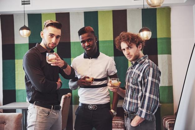 Młodzi wieloetniczni ludzie świętują i piją toast whisky Premium Zdjęcia