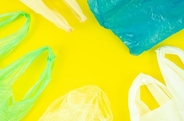Mnóstwo kolorowych plastikowych toreb na żółtym tle Darmowe Zdjęcia