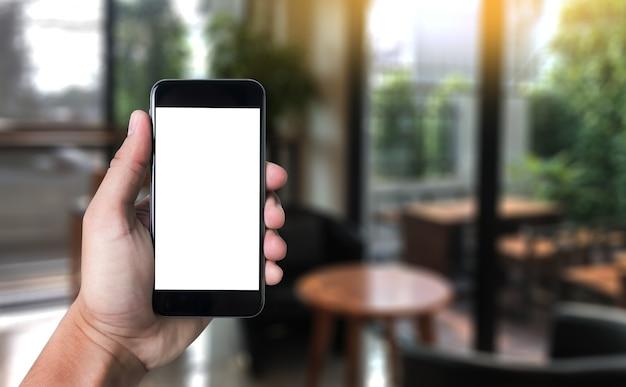 Mockup Mobilny Wizerunek Ręka Telefon Z Pustym Bielu Ekranu Rocznika Brzmieniem. Premium Zdjęcia