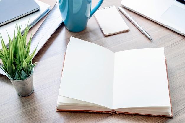 Mockup otwarty notatnik z pustą stroną, laptopem i dostawami na drewnianym stole. Premium Zdjęcia