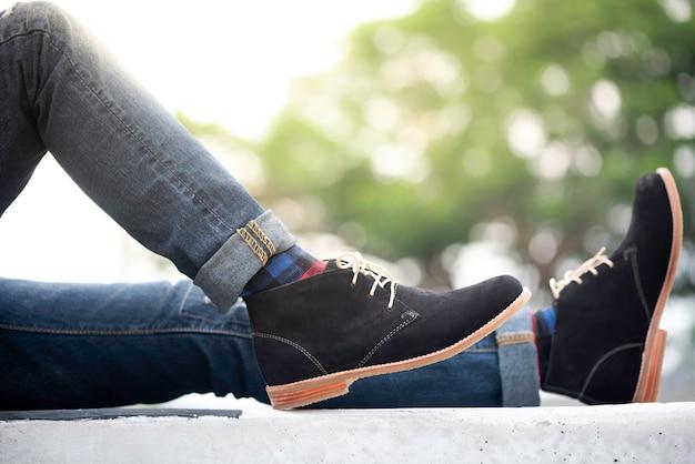 Moda Mężczyzna Nosi Dżinsy I Czarne Buty Premium Zdjęcia