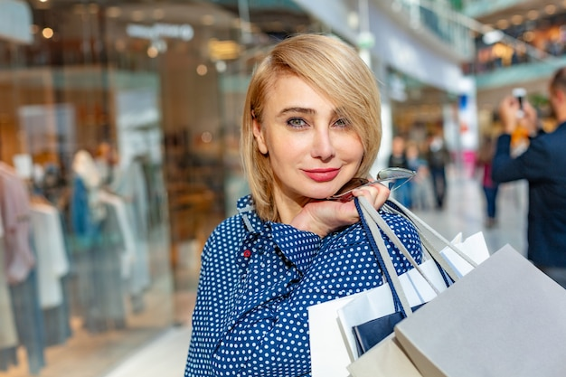 Moda na zakupy portret dziewczyny. piękna kobieta z torby na zakupy w centrum handlowym. klient. obroty. Premium Zdjęcia