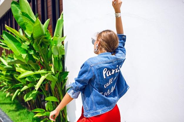 Moda Na Zewnątrz Portret Oszałamiającej Blondynki, Ubrana W Luksusową Elegancką Suknię Wieczorową, Okulary Przeciwsłoneczne Zarobków. I Kurtka Hipster, Tropikalne Liście Na Tle. Darmowe Zdjęcia