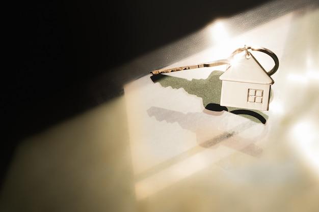 Model domu i klucz do domu światłem z okna. dom oferujący agent nieruchomości, Premium Zdjęcia