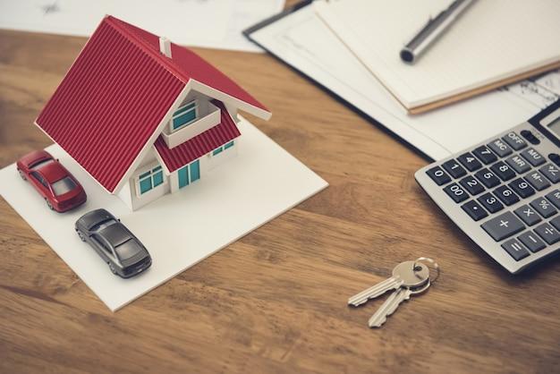 Model domu, klucz i kalkulator z dokumentami na stole Premium Zdjęcia