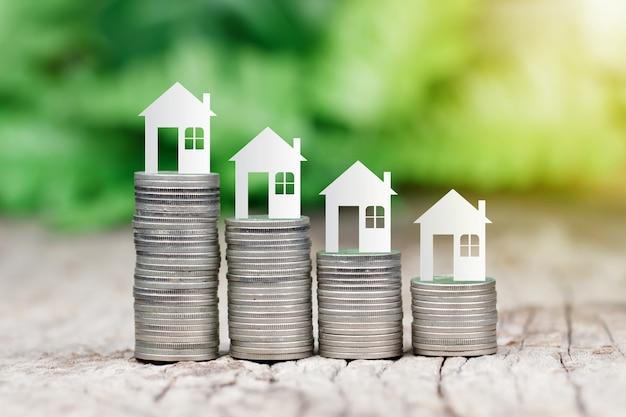 Model domu na stosie monet do oszczędzania na zakup domu Premium Zdjęcia