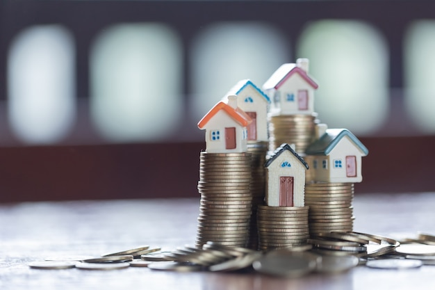 Model domu na stosie monet. koncepcja drabiny nieruchomości, hipoteki i inwestycji w nieruchomości. Premium Zdjęcia