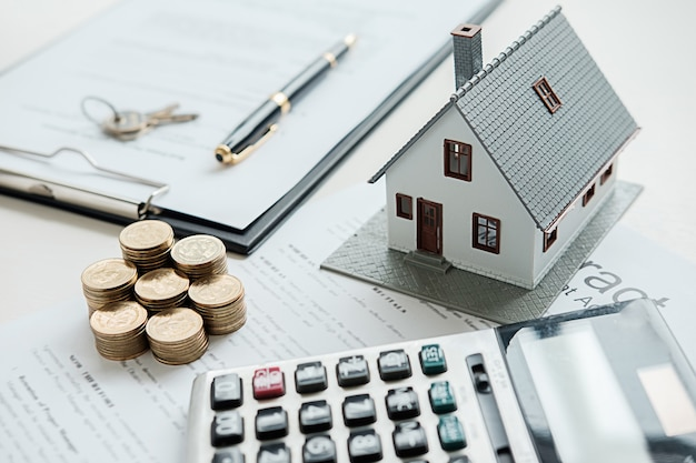 Model domu z agentem nieruchomości i klientem dyskusji na temat umowy na zakup domu, ubezpieczenia lub pożyczki w tle nieruchomości. Premium Zdjęcia