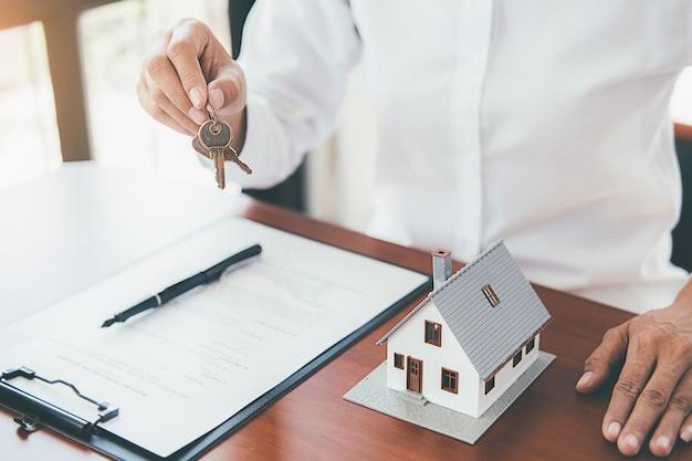 Model domu z agentem nieruchomości i klientem omawiającym umowę na zakup domu Premium Zdjęcia