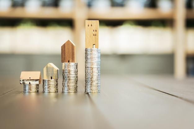 Model domu z drewna i rząd monet pieniędzy na białym tle, Premium Zdjęcia