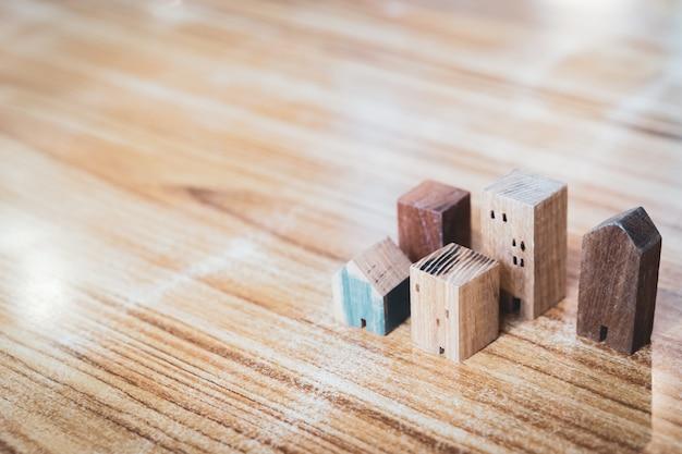 Model domu z drewna na tle drewna, symbol budowy Premium Zdjęcia
