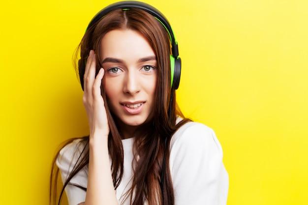 Model Piękna Młoda Dziewczyna Słucha Muzyki W Słuchawkach Na żółty Premium Zdjęcia
