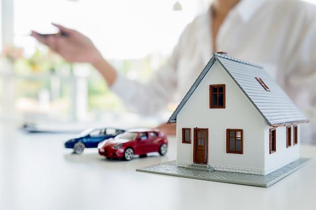 Model samochodu i domu z agentem i klientem omawiającym umowę na zakup, uzyskanie ubezpieczenia lub pożyczki na nieruchomości lub nieruchomości. Premium Zdjęcia