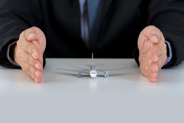 Model samolotu wspiera ręce na biurku, samolot ochronny bezpieczny Premium Zdjęcia