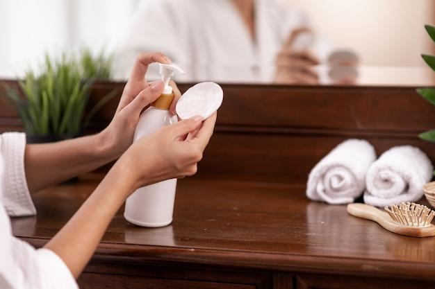Model W Białym Szlafroku Wyciska Produkt Z Białej Butelki, Która Stoi Na Brązowej Drewnianej Toalecie, Na Której Znajdują Się Ręczniki, Grzebień I Stojak Na Doniczki, Na Waciku. Zbliżenie. Premium Zdjęcia