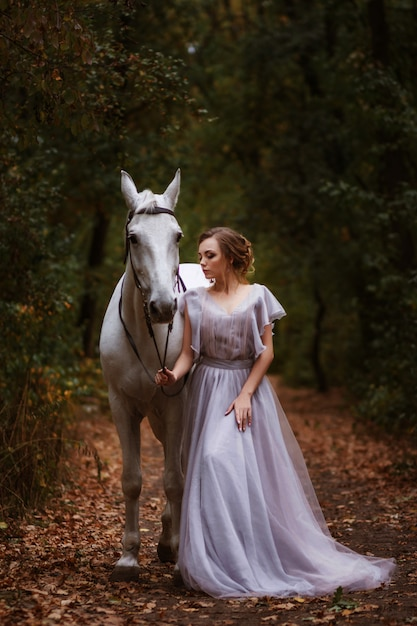 Modelka W Delikatnej Sukience Z Białym Koniem W Pobliżu W Bajecznym Zielonym Lesie. Premium Zdjęcia
