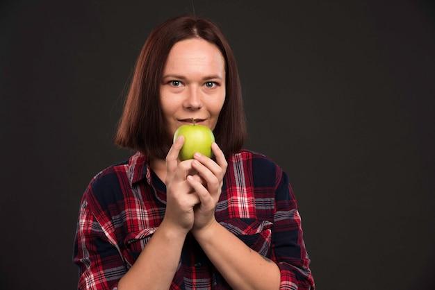 Modelka W Jesienno-zimowej Kolekcji Strojów Trzyma Zielone Jabłko I Czuje Się Podekscytowana. Darmowe Zdjęcia