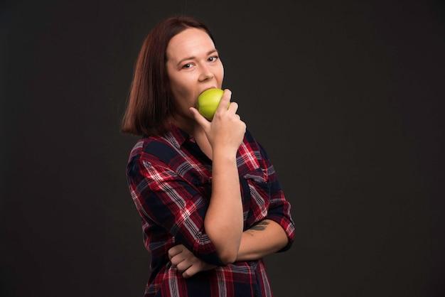 Modelka W Jesienno-zimowej Kolekcji Strojów Trzyma Zielone Jabłko I Gryzie. Darmowe Zdjęcia
