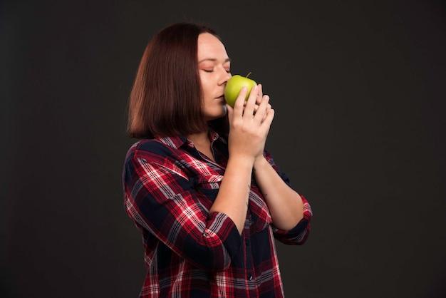 Modelka W Jesienno-zimowej Kolekcji Strojów Trzyma Zielone Jabłko I Wącha Je. Darmowe Zdjęcia