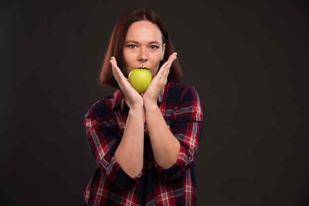 Modelka W Jesienno-zimowej Kolekcji Strojów Trzyma Zielone Jabłko Na Ustach. Darmowe Zdjęcia