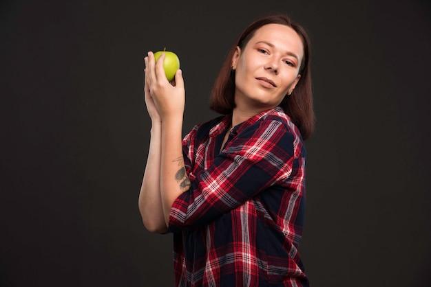 Modelka W Kolekcji Jesień Zima Stroje Trzymając Zielone Jabłko I Ciesząc Się Nim. Darmowe Zdjęcia
