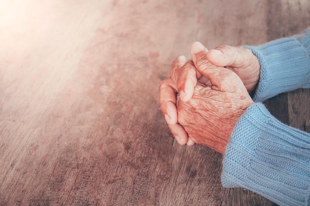 Modląca się ręka starej osoby. koncepcja: nadzieja, wiara, dramatyczna samotność, smutek, depresja, płacz, rozczarowanie, opieka zdrowotna, ból. Premium Zdjęcia