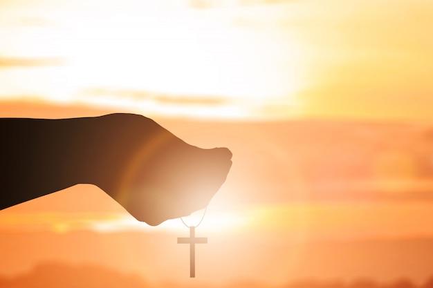 Modlitwa ludzką ręką z krzyżem chrześcijańskim Premium Zdjęcia