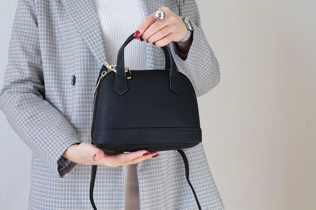 Modna Kobieta Trzyma Czarną Skórzaną Torbę. Miejsce Na Twój Tekst Premium Zdjęcia