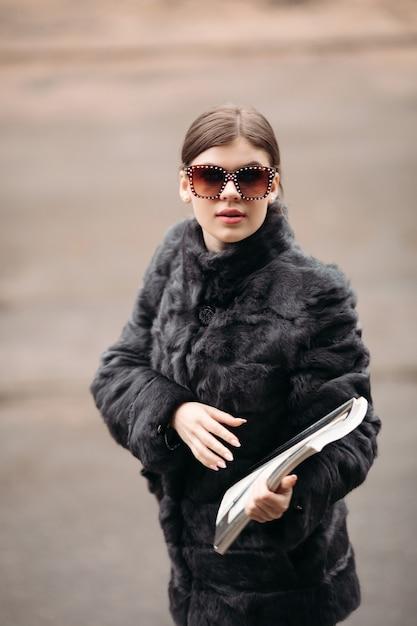 Modna Kobieta W Futrze I Okulary Przeciwsłoneczne, Pozowanie Na Ulicy Premium Zdjęcia