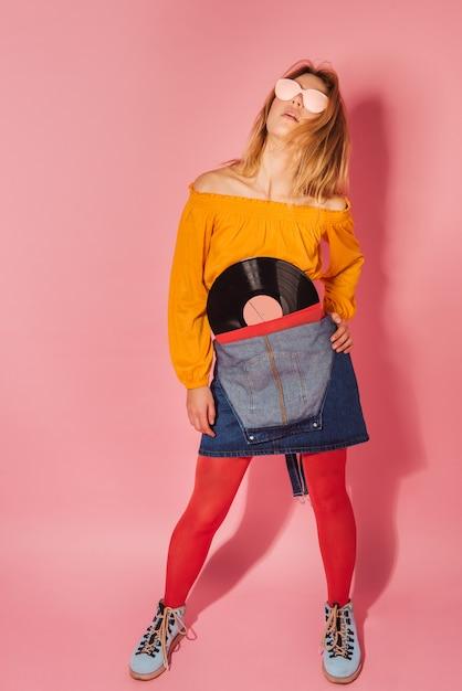 Modna Kobieta W Stylu Retro Z Rocznika Winylu Na Różowym Tle Premium Zdjęcia