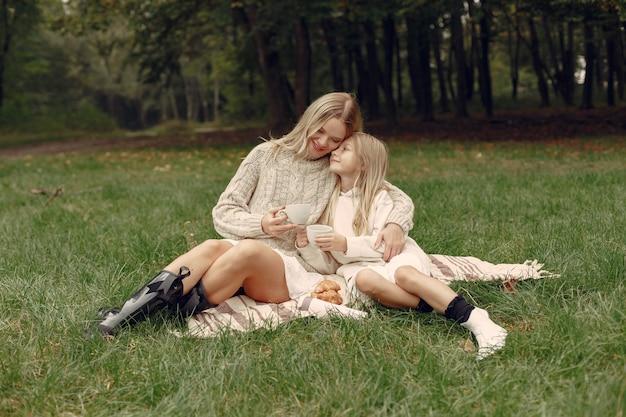 Modna Matka Z Córką. Ludzie Siedzący Na Trawie Darmowe Zdjęcia