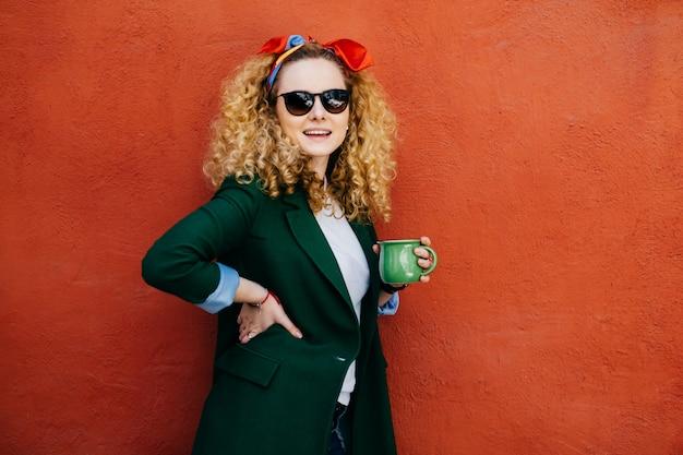 Modna młoda piękna kobieta z puszystymi blond włosami na sobie pałąk, okulary przeciwsłoneczne i kurtkę. Premium Zdjęcia