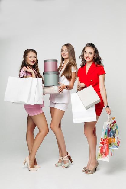 Modne dziewczyny po zakupach zaskoczyły patrząc na torby. Premium Zdjęcia
