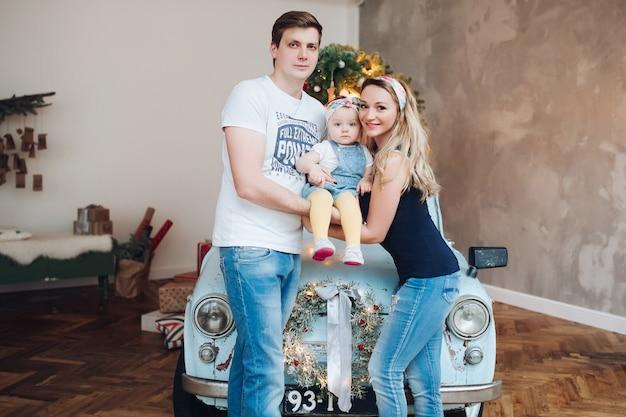 Modni Rodzice Trzyma Dalej Małą śliczną Córkę, Stoi Blisko Błękitnego Retro Samochodu. Premium Zdjęcia