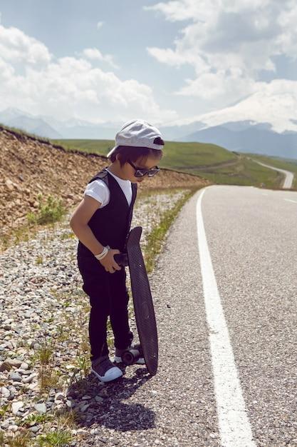 Modny Chłopiec Dziecko W Białej Czapce Trampki I Kamizelce Stoi Z łyżwą Na Drodze W Górach Mount Everest Latem Premium Zdjęcia