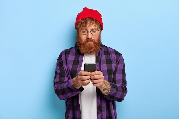 Modny Hipster Z Rudymi Włosami I Gęstą Brodą, Skupiony Na Smartfonie, Otrzymuje Link Do Jakiejś Publikacji Darmowe Zdjęcia