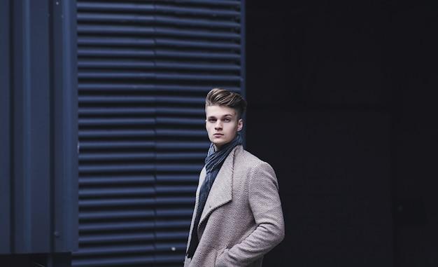 Modny Mężczyzna Stoi Na Ulicy W Płaszczu. Zimowy, Jesienny Strój. Premium Zdjęcia