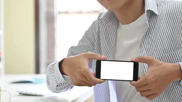 Modny młody człowiek pokazuje pustego ekran jego telefon komórkowy Premium Zdjęcia