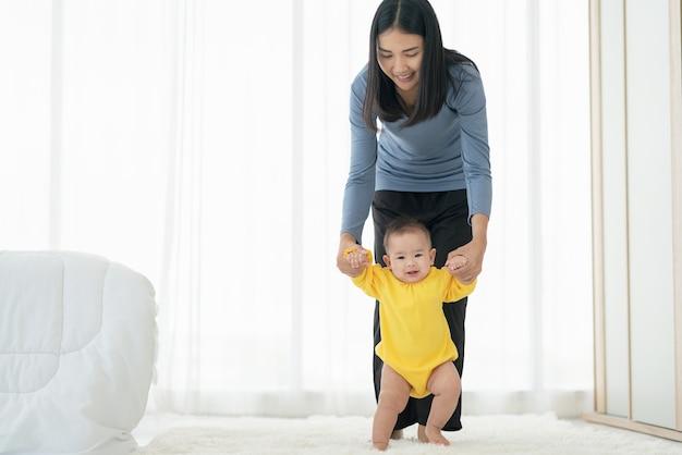 Moja Mała Dziewczynka Stawia Pierwsze Kroki. Rodzina Szczęśliwe Małe Dziecko Uczy Się Chodzić Z Pomocą Matki W Domu Premium Zdjęcia