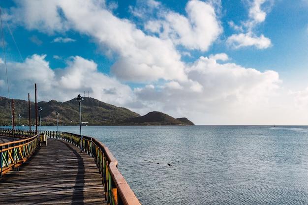 Molo Na Morzu Otoczone Górami Pod Błękitnym Pochmurnym Niebem I światłem Słonecznym Darmowe Zdjęcia